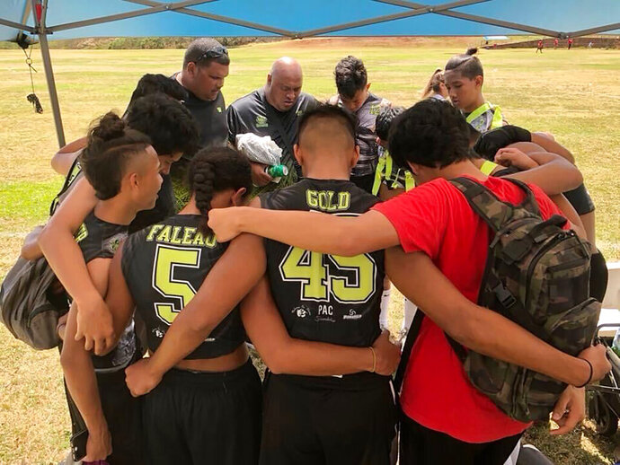 CORRECTS SPELLING OF FIRST NAME TO KINOHI INSTEAD OF KANOHI - This 2017 photo provided by Ke'ala Aki shows Willie Talamoa, rear center with shaved head, next to Kinohi Aki, rear left, as they pray with players from their 15-and-under flag football team in Honolulu. A Honolulu community is mourning the loss of Talamoa, a mentor, football coach and father figure who died after contracting COVID-19. (Ke'ala Aki via AP)