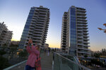 FILE - In this Friday, July 6, 2018 file photo, a woman on the bridge takes a selfie with The Twins buildings in the background, one of a number of new high-rises transforming the skyline view, in the southern coastal city of Limassol in the eastern Mediterranean island of Cyprus. Cyprus government spokesman Kyriakos Koushos said on Tuesday, Oct. 13, 2020, that the Cabinet accepted a recommendation by the minsters of the interior and finance to cancel altogether the