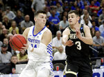 Kentucky's Tyler Herro, left, looks to pass as he is guarded by Wofford's Fletcher Magee (3) during the first half of a second-round game in the NCAA men's college basketball tournament in Jacksonville, Fla., Saturday, March 23, 2019. (AP Photo/John Raoux)