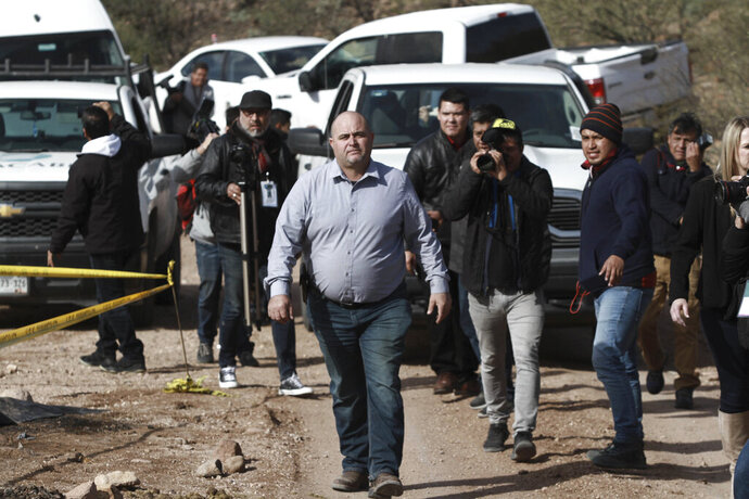 Julian Le Baron arrives where one of the cars belonging to the extended LeBaron family was ambushed by gunmen last year near Bavispe, Sonora state, Mexico, Sunday Jan. 12, 2020. Lopez Obrador said Sunday there is an agreement to establish a monument will be put up to memorialize nine U.S.-Mexican dual citizens ambushed and slain last year by drug gang assassins along a remote road near New Mexico. (AP Photo/Christian Chavez)