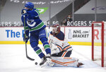 Edmonton Oilers goalie Mikko Koskinen, right, of Finland, makes the save while being screened by Vancouver Canucks' Brock Boeser during the second period of an NHL hockey game, Monday, May 3, 2021, in Vancouver, British Columbia. (Darryl Dyck/The Canadian Press via AP)