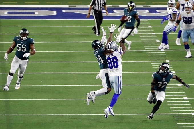 Philadelphia Eagles cornerback Darius Slay (24) leaps upward in front of Dallas Cowboys wide receiver CeeDee Lamb (88) to intercept a pass thrown by Cowboys quarterback Andy Dalton in the second half of an NFL football game in Arlington, Texas, Sunday, Dec. 27. 2020. (AP Photo/Roger Steinman)
