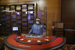 Plexiglass surrounds a blackjack dealer at the MGM Grand Detroit casino, Wednesday, Aug. 5, 2020, in Detroit. Detroit's three casinos will start reopening Wednesday under new governor-mandated capacity restrictions, months after closing for the coronavirus pandemic. MotorCity Casino Hotel and the Greektown Casino-Hotel. opened Wednesday. MGM Grand Detroit will open for invite-only VIP customers Wednesday and Thursday, and at 10 a.m. Friday for the general public. (AP Photo/Carlos Osorio)
