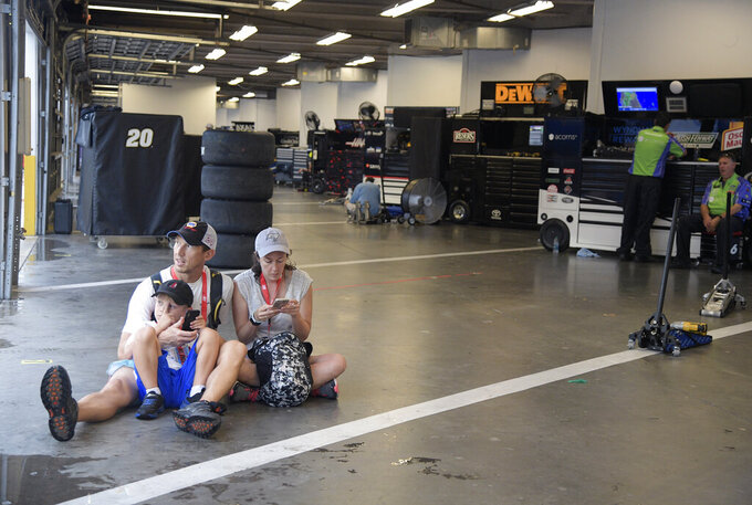Garrett Kulczycki, left, his son Corbin, 6, and Susan Beach take shelter in the garage area during a weather delay before the NASCAR Cup Series auto race at Daytona International Speedway, Saturday, July 6, 2019, in Daytona Beach, Fla. (AP Photo/Phelan Ebenhack)