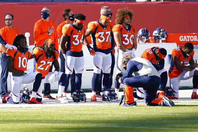 The Denver Broncos stand and kneel during the national anthem prior to an NFL football game against the Los Angeles Chargers, Sunday, Nov. 1, 2020, in Denver. (AP Photo/David Zalubowski)