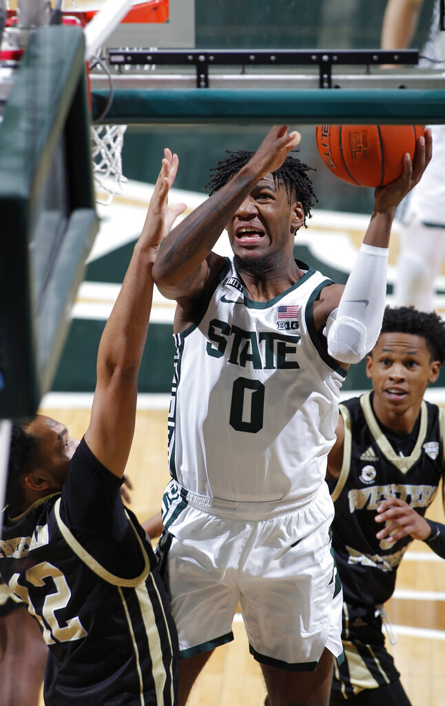 Michigan State's Aaron Henry (0) goes to the basket against Western Michigan's Josiah Freeman during the second half of an NCAA college basketball game, Sunday, Dec. 6, 2020, in East Lansing, Mich. (AP Photo/Al Goldis)