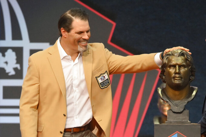 Steve Hutchinson, a member of the Pro Football Hall of Fame Centennial Class, puts his hand on his bust during the induction ceremony at the Pro Football Hall of Fame, Saturday, Aug. 7, 2021, in Canton, Ohio. (AP Photo/David Richard)