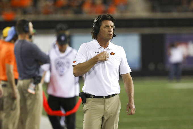 Oklahoma State head coach Mike Gundy watches the scoreboard during the second half of an NCAA college football game with Oregon State in Corvallis, Ore., Friday, Aug. 30, 2019. Oklahoma State won 52-36. (AP Photo/Amanda Loman)