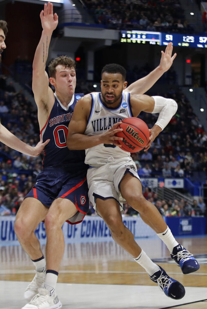 Villanova's Phil Booth, right, drives on St. Mary's Tanner Krebs, left, during the second half of a first round men's college basketball game in the NCAA Tournament, Thursday, March 21, 2019, in Hartford, Conn. (AP Photo/Elise Amendola)