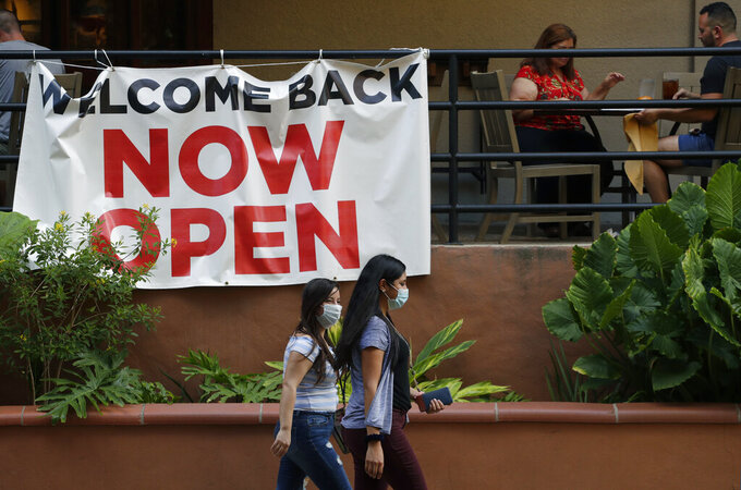 FILE - In this May 27, 2020, file photo, visitors to the River Walk pass a restaurant that has reopened in San Antonio. Coronavirus cases are rising in nearly half the U.S. states, as states are rolling back lockdowns. (AP Photo/Eric Gay, File)