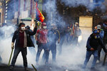 A supporter of former President Evo Morales stands holding a Wiphala flag, in clouds of tear gas during clashes with police in La Paz, Bolivia, Friday, Nov. 15, 2019. Morales stepped down on Sunday following nationwide protests over suspected vote-rigging in an Oct. 20 election in which he claimed to have won a fourth term in office. An Organization of American States audit of the vote found widespread irregularities. (AP Photo/Natacha Pisarenko)