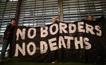Demonstrators hold a banner during a vigil for the 39 lorry victims, outside the Home Office in London, Thursday, Oct. 24, 2019. Authorities found 39 people dead in a truck in an industrial park in England on Wednesday and arrested the driver on suspicion of murder in one of Britain's worst human-smuggling tragedies. (AP Photo/Kirsty Wigglesworth)