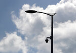 In this photo taken July 17, 2019, a high-tech video camera hangs from a lamppost in Belgrade, Serbia.  A video surveillance system with facial recognition by Chinese tech giant Huawei is being rolled out across hundreds of cities worldwide, particularly in poor countries with weak track records on human rights where Beijing has increased its influence through big business deals. (AP Photo/Darko Vojinovic)