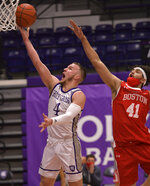 Holy Cross' Austin Butler leaps for a shot with Boston's Sukhmail Mathon blocking during an NCAA college basketball game Monday, Jan. 4, 2021, in Worcester, Mass. (Christine Peterson/Worcester Telegram & Gazette via AP)