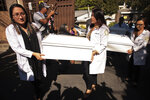 Small coffins holding the remains of three of six family members who were killed in a 1982 massacre are carried by workers from the forensic office to be handed over to the victims' family in San Salvador, El Salvador, Thursday, Jan. 23, 2020. The remains of six adults and children from one family were handed over to surviving relatives Thursday, 38 years after the El Calabozo massacre, in which government soldiers are accused of killing more than 200 people. (AP Photo/Salvador Melendez)