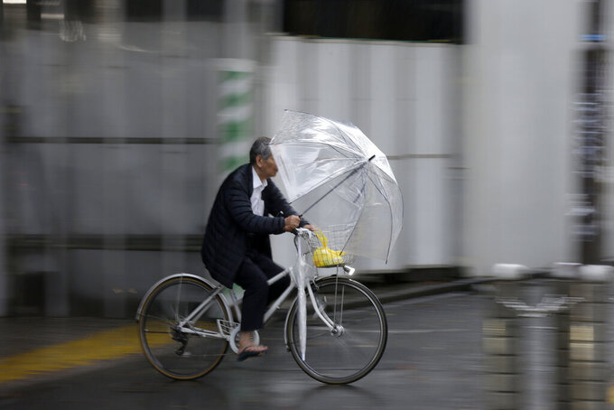 A man holds an umbrella while ride his bicycle in rain in Shibuya district, Tokyo Saturday, Oct. 12, 2019. Tokyo as surrounding areas braced for a powerful typhoon forecast as the worst in six decades, with streets and trains stations unusually quiet Saturday as rain poured over the city. (AP Photo/Kiichiro Sato)