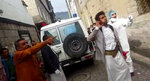 This May 2020 frame grab from video provided by a Yemeni Community activist, shows an activist wearing protective gear and others arguing with a person in the neighborhood, while collecting the lifeless body of a COVID-19 victim, after medics declined to take the body, in the Houthi-controlled city of Ibb, Yemen. (Courtesy of a Yemeni Community Activist via AP)