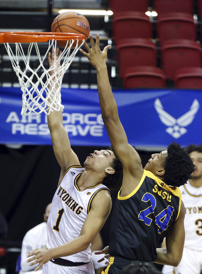 Wyoming guard Marcus Williams (1) shoots as San Jose State forward Michael Ofoegbu (24) defends during the second half of an NCAA college basketball game in the first round of the Mountain West Conference men's tournament Wednesday, March 10, 2021, in Las Vegas. (AP Photo/Isaac Brekken)