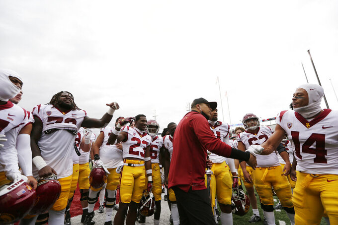 Southern California interim head coach Donte Williams, center, celebrates with his team after their 45-14 win over Washington State in an NCAA college football game, Saturday, Sept. 18, 2021, in Pullman, Wash. (AP Photo/Young Kwak)