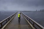 Storm chaser Shaun Piegdon walks down a pier over Lake Arthur as Hurricane Delta's outer bands move into Louisiana, Friday, Oct. 9, 2020. Residents in south Louisiana braced to relive a nightmare Friday as bands of rain from approaching Hurricane Delta began soaking the same area of the state that was badly battered by a deadly hurricane six weeks ago. (Chris Granger/The Advocate via AP)