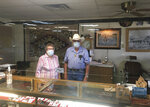 "In this photo provided by the Billy The Kid Museum, Lula Sweet, 86, and Don Sweet, 87, pose for a photo behind Plexiglas at the cash register at the Billy The Kid Museum gift shop in Fort Sumner, N.M., in De Baca county, Thursday, July 9, 2020. De Baca is one of two counties in the state where no coronavirus cases have been confirmed. ""Most everybody tries to respect each other's space,"" says the Sweets' son, Tim, who runs the museum. (Tim Sweet/Billy The Kid Museum via AP)"