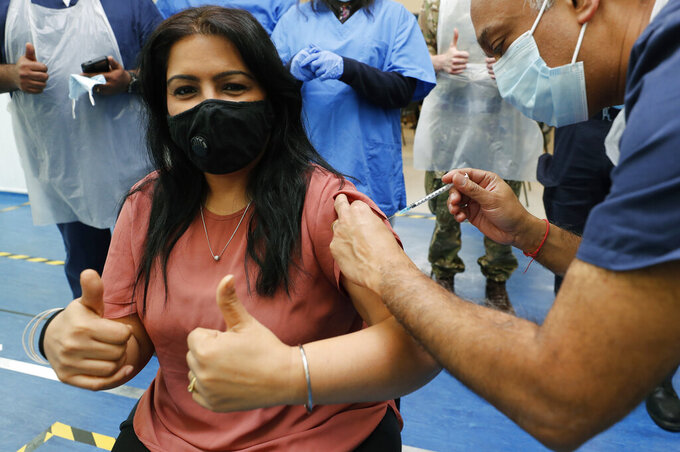 Doctor Anil Mehta, surrounded by his team of doctors, administers a dose of the Pfizer vaccine to Geeta Waddon to mark the 10,000th jab in his small practice in London, Sunday, Feb. 28, 2021. (AP Photo/Frank Augstein)