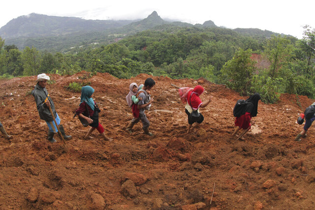 Villagers make their way at an area affected by a landslide in Sukajaya, West Java, Indonesia, Sunday, Jan. 5, 2020. Landslides and floods triggered by torrential downpours have left dozens of people dead in and around Indonesia's capital, as rescuers struggled to search for people apparently buried under tons of mud, officials said Saturday. (AP Photo/Ar Rayyan)