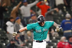 Seattle Mariners' Jarred Kelenic reacts to the home run of Mitch Haniger as he heads in to score against the Cleveland Indians during the seventh inning of a baseball game Friday, May 14, 2021, in Seattle. (AP Photo/Elaine Thompson)