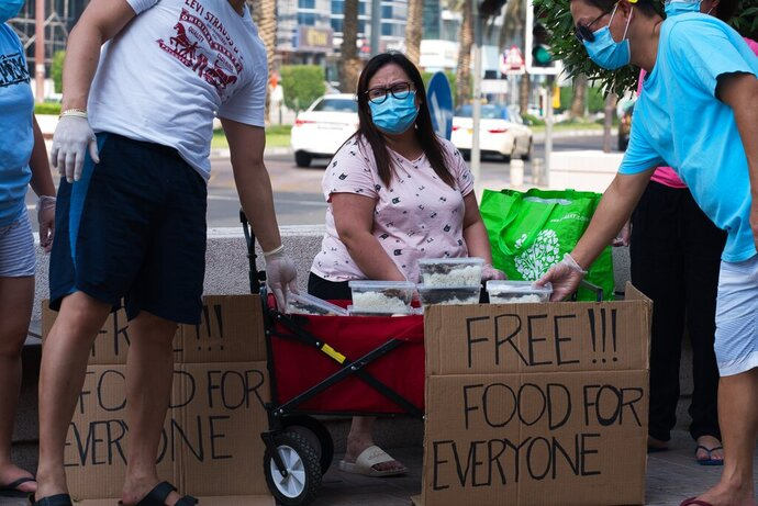 In this Wednesday, June 3, 2020 photo, Feby Cachero Baguisa Dela Pena of Laguna, Philippines, hands out free food to those who need it in Dubai, United Arab Emirates. Dela Pena, a mother of three, is unemployed, but when she saw people lining up for free meals one night outside her building two weeks ago she decided to use whatever money her family had to help out the countless numbers of Filipinos and others who've lost jobs amid the coronavirus. (AP Photo/Jon Gambrell)