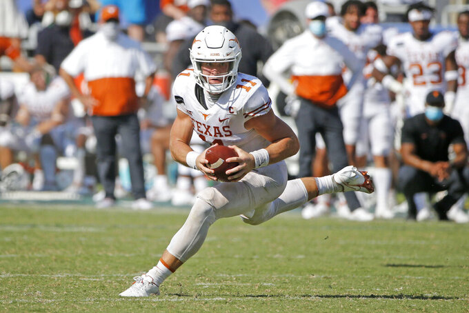 Texas quarterback Sam Ehlinger scrambles during the second half of the team's NCAA college football game against Oklahoma in Dallas, Saturday, Oct. 10, 2020. Oklahoma won 53-45 in four overtimes.(AP Photo/Michael Ainsworth)