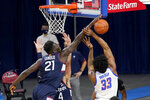 Connecticut's Adama Sanogo (21) blocks a shot by DePaul's Pauly Paulicap during the first half of an NCAA college basketball game Monday, Jan. 11, 2021, in Chicago. (AP Photo/Charles Rex Arbogast)