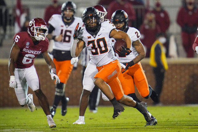 Oklahoma State running back Chuba Hubbard (30) carries past Oklahoma cornerback Tre Brown (6) during the first half of an NCAA college football game in Norman, Okla., Saturday, Nov. 21, 2020. (AP Photo/Sue Ogrocki)
