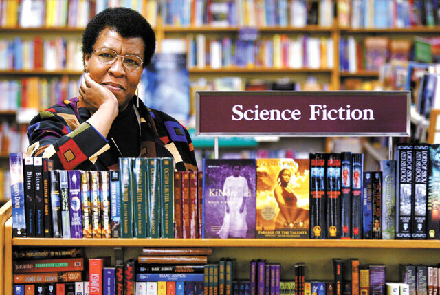 FILE - In this Feb. 4, 2004 file photo, author Octavia Butler poses near some of her novels at University Book Store in Seattle, Wash. Butler, considered the first black woman to gain national prominence as a science fiction writer, died Feb. 24, 2006, at age 58. Fourteen years after her death, Butler has never seemed more relevant. The rare black science fiction writer in her lifetime, she is now praised for anticipating many of the major issues of the day, from pandemics to the election of Donald Trump. (Joshua Trujillo/seattlepi.com via AP, File)