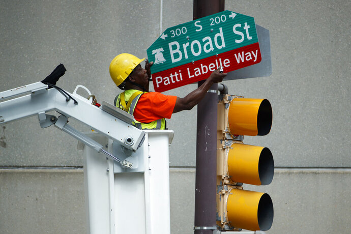 A worker hangs a street sign before a ceremony honoring singer Patti LaBelle, Tuesday, July 2, 2019, in Philadelphia. A stretch of Broad Street, between Locust and Spruce Streets, will be renamed