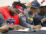 Evan Anderson, left, committing to Florida Atlantic University, and Avarius Sparrow, committing to West Virginia, sign their commitment papers during a National Signing Day ceremony at Jones High School, Wednesday, Feb. 5, 2020, in Orlando, Fla. (Joe Burbank