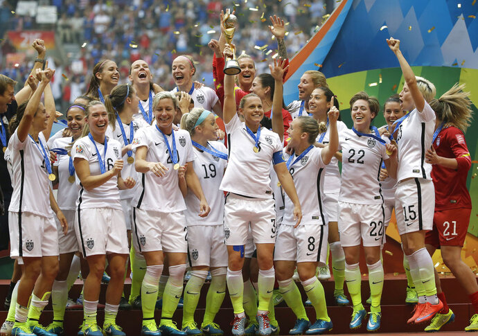 FILE - In this Sunday, July 5, 2015, file photo, the U.S. team celebrates with the trophy after it defeated Japan 5-2 in the FIFA Women's World Cup soccer championship in Vancouver, British Columbia. FIFA is rolling out a global strategy to grow the women's game in advance of next year's World Cup in France. Soccer's governing body has been ramping up its attention to the women's side of the sport for the past several years, partly in response to calls for more equity. The result is a five-pronged proposal that starts at the ground level among FIFA's 211 member associations, FIFA Chief Women's Football Officer Sarai Bareman said. (AP Photo/Elaine Thompson, File)