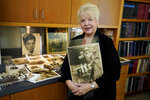 """Diane Capone holds a copy of a photograph of her father, Albert """"Sonny"""" Capone as a young boy and her grandfather Al Capone on display at Witherell's Auction House in Sacramento, Calif., Wednesday, Aug. 25, 2021. The granddaughter of the famous mob boss and her two surviving sisters will sell 174 family heirlooms at an Oct. 8 auction titled """"A Century of Notoriety: The Estate of Al Capone,"""" that will be held by Witherell's in Sacramento. (AP Photo/Rich Pedroncelli)"""