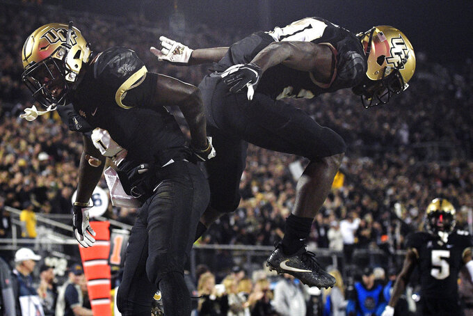 Central Florida running back Greg McCrae (30) celebrates with running back Adrian Killins Jr. (9) after McCrae rushed for a 9-yard touchdown during the second half of an NCAA college football game against Cincinnati Saturday, Nov. 17, 2018, in Orlando, Fla. Central Florida won, 38-13. (AP Photo/Phelan M. Ebenhack)