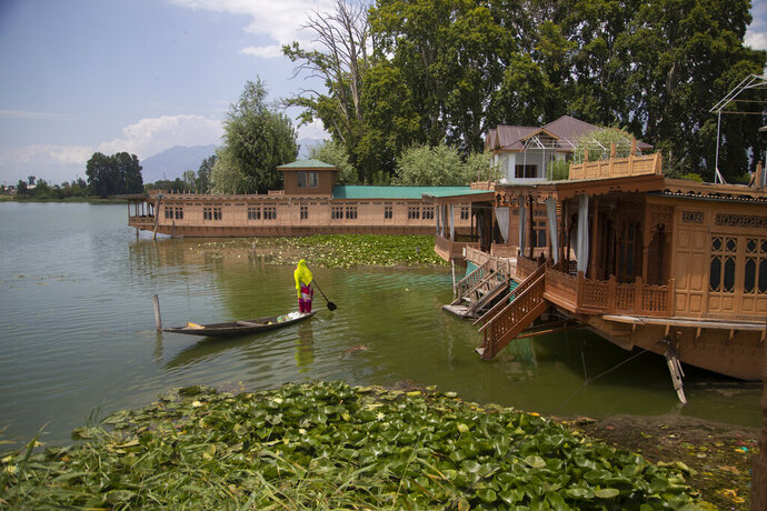 A Kashmiri woman rows her boat near unoccupied houseboats at Nigeen Lake in Srinagar, Indian controlled Kashmir, July 16, 2020. Indian-controlled Kashmir's economy is yet to recover from a colossal loss a year after New Delhi scrapped the disputed region's autonomous status and divided it into two federally governed territories. (AP Photo/Mukhtar Khan)