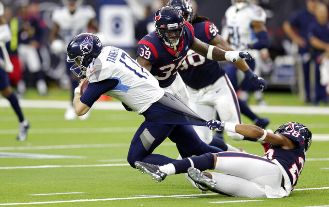 Houston Texans cornerback Vernon III Hargreaves (28) grabs the shirt of Tennessee Titans quarterback Ryan Tannehill (17) as he tries to tackle him during the first half of an NFL football game Sunday, Dec. 29, 2019, in Houston. (AP Photo/Michael Wyke)