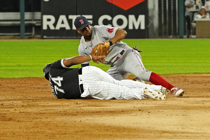 Boston Red Sox shortstop Xander Bogaerts, top, tags out Chicago White Sox's Eloy Jimenez (74) at second base during the third inning of a baseball game, Friday, Sept. 10, 2021, in Chicago. (AP Photo/David Banks)