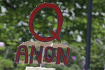 FILE - In this May 14, 2020 file photo, a person carries a sign supporting QAnon at a protest rally in Olympia, Wash.  Walmart, Amazon and other corporate giants donated money to a Tennessee state lawmaker's re-election campaign after she used social media to amplify and promote the QAnon conspiracy theory. That's according to an Associated Press review of campaign finance records and online posts by Republican state Rep. Susan Lynn. (AP Photo/Ted S. Warren, File)