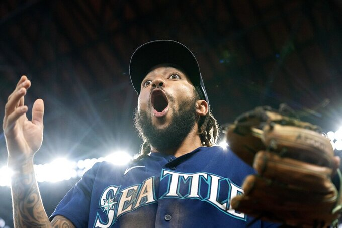 Seattle Mariners' J.P. Crawford (3) gestures to fans in the middle of the eighth inning of a baseball game against the Texas Rangers, Thursday, Aug. 19, 2021, in Arlington, Texas. Seattle won 9-8. (AP Photo/Jeffrey McWhorter)
