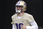 FILE - In this April 3, 2019, file photo, Washington quarterback Jacob Eason jogs to the field for NCAA college football practice in Seattle. Eason replaces Jake Browning, who threw for 3,192 yards with 16 touchdowns last season, leading the Huskies to a 10-4 record and the Pac-12 championship. Browning now plays for the NFL's Minnesota Vikings.(AP Photo/Ted S. Warren, File)