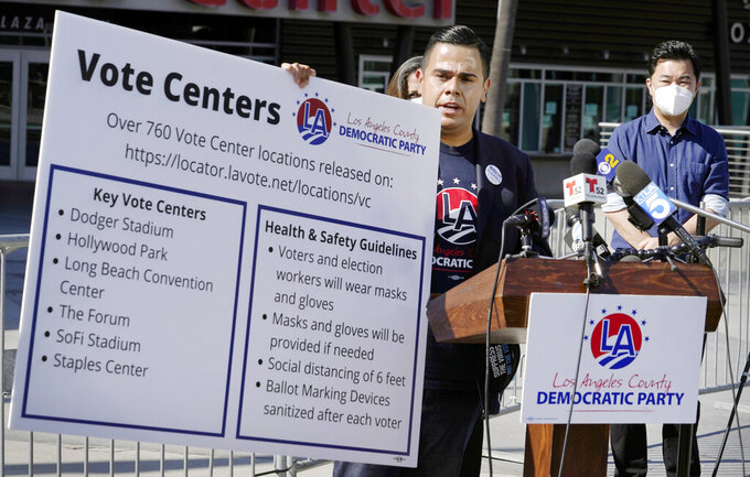FILE - In this Oct. 1, 2020 file photo, Los Angeles County Democratic Party Chair Mark J. Gonzalez, center, flanked by Los Angeles City Councilmember David Ryu, right, and others, holds a banner with key vote center locations and social distancing instructions at a news conference outside Staples Center in Los Angeles. Most vote centers in California will open on Saturday. There will be fewer of them available this year because of the coronavirus. While most people will vote by mail, some will still show up to vote in person. State officials are urging people to vote early to avoid lines. (AP Photo/Damian Dovarganes, File)