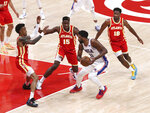 Atlanta Hawks players John Collins, left, Clint Capela (15) and Solomon Hill (18) triple-team against Philadelphia 76ers center Joel Embiid (21) to slow his drive in Game 3 of a second-round NBA basketball playoff series, Friday, Jun 11, 2021, in Atlanta. (Curtis Compton/Atlanta Journal-Constitution via AP)
