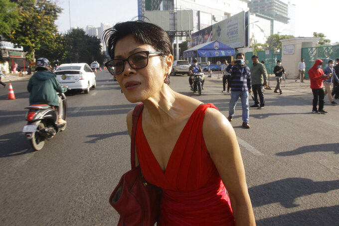 Theary Seng, a Cambodian-American lawyer, stands near the Phnom Penh Municipal Court in Phnom Penh, Cambodia, Thursday, Jan. 14, 2021. Theary Seng said Thursday she was being persecuted for her political opinion as she and dozens of other government critics charged with treason and other offenses returned to court in a trial criticized by rights advocates. (AP Photo/Heng Sinith)
