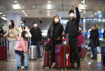 Travelers wear face masks as they stand in the arrivals area at Beijing Capital International Airport in Beijing, Thursday, Jan. 23, 2020. China closed off a city of more than 11 million people Thursday, halting transportation and warning against public gatherings, to try to stop the spread of a deadly new virus that has sickened hundreds and spread to other cities and countries in the Lunar New Year travel rush. (AP Photo/Mark Schiefelbein)