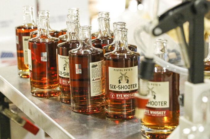 This Nov. 3, 2020 image provided by New Mexico State University shows bottles of the school's new officially licensed spirit, Pistol Pete's Six Shooter Rye Whiskey, being filled at Dry Point Distillers in Las Cruces, New Mexico. The whiskey is part of the school's latest branding and licensing project. (Charlie Hurley, New Mexico State University, via AP)