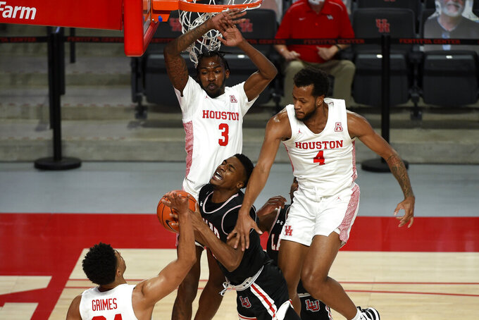 Lamar forward Lincoln Smith, center, is fouled by Houston forward Justin Gorham (4) during the first half of an NCAA college basketball game, Wednesday, Nov. 25, 2020, in Houston. (AP Photo/Eric Christian Smith)